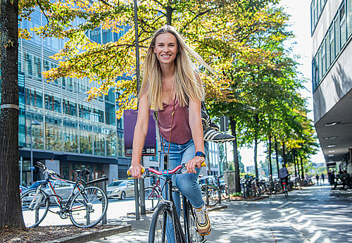 Junge blonde Frau auf dem Fahrrad